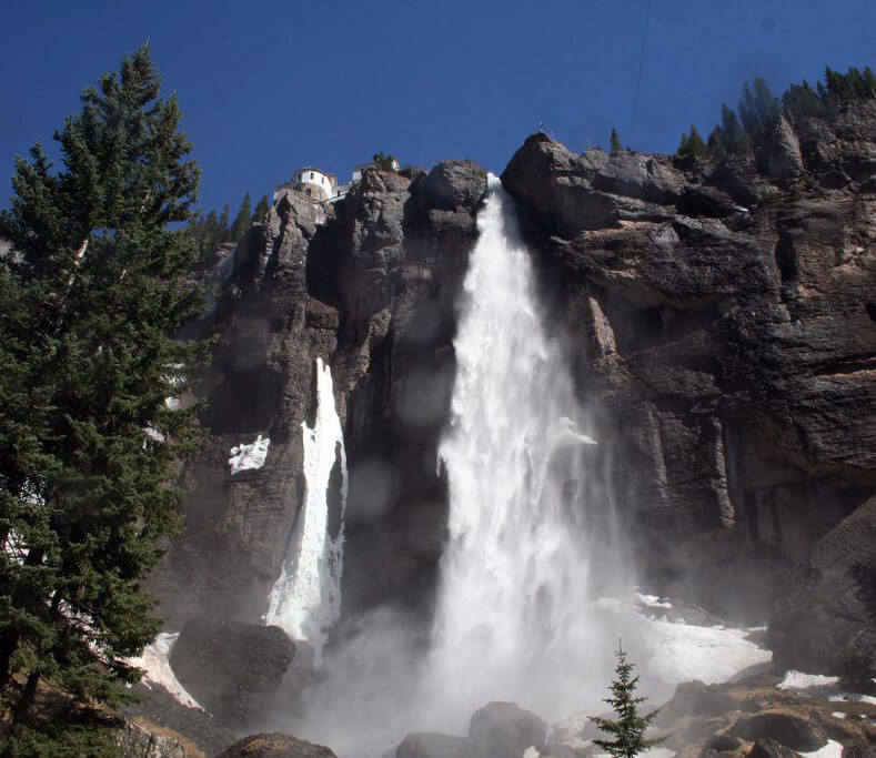 move to colorado veil falls tourist attraction large white waterfall over cliff with pine tree
