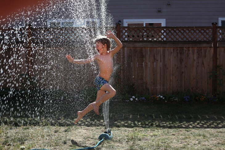 Boy playing with the sprinkler