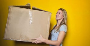 reasons to move to colorado blonde woman holding large cardboard box yellow background