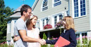 colorado buyers agent shaking hands with couple in front of their new home