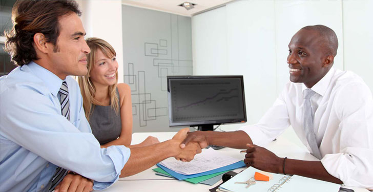 colorado buyers agent shaking hands with happy couple in office sitting down with paperwork and computer charts