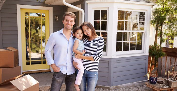 young colorado happy couple and baby in backyard of new home with moving boxes